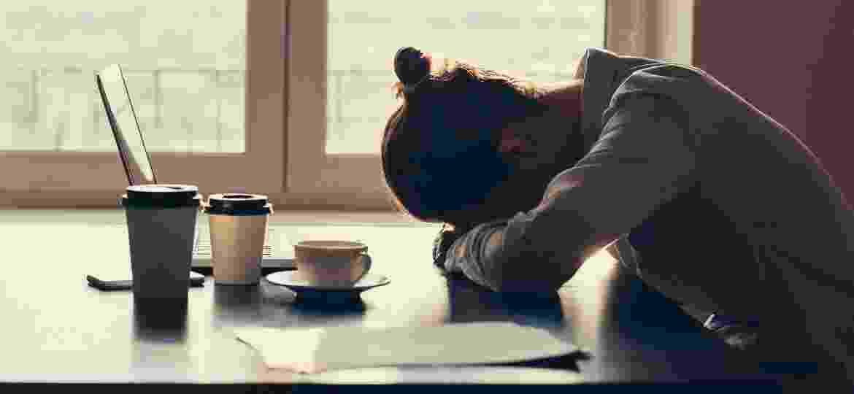 mulher cansada trabalhando trabalho computador laptop notebook perdeu celular - iStock