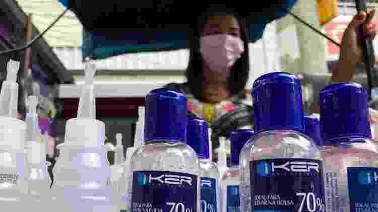 24.mar.2020 - Ambulante Adriana Ferreira oferece álcool em gel e máscaras para a população na Via Ápia, na Rocinha - Herculano Barreto Filho/UOL - Herculano Barreto Filho/UOL