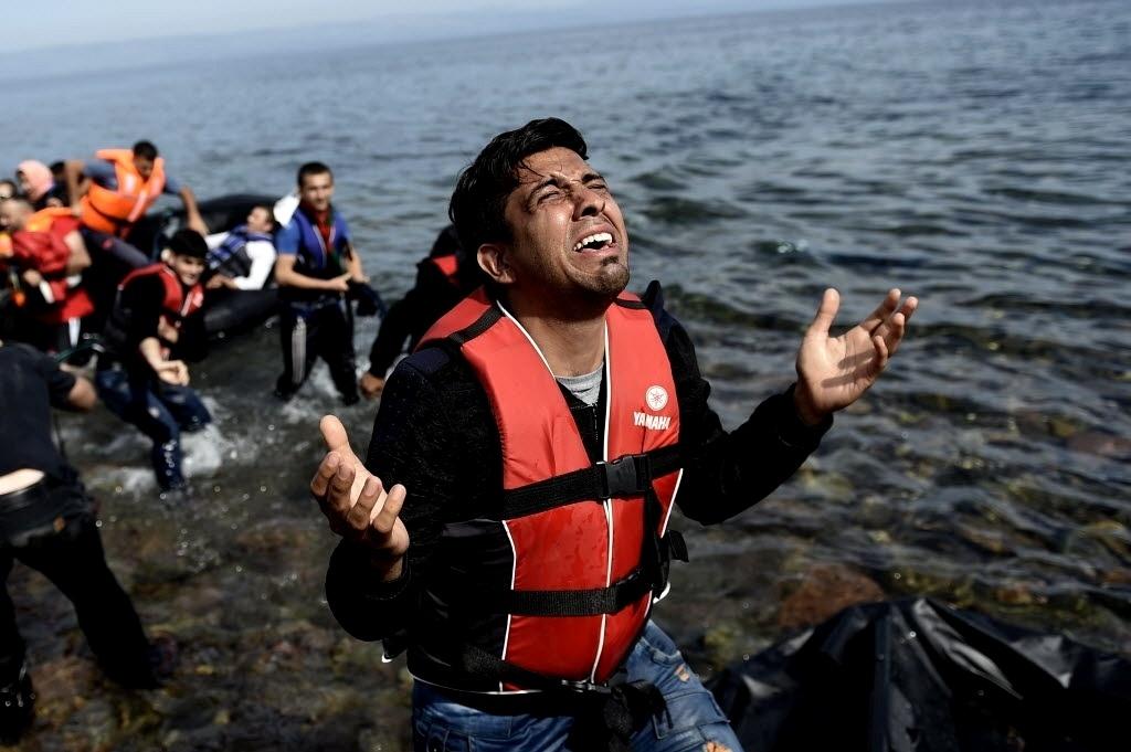 27.set.2015 - Homem ora após pisar em terra firme na ilha grega de Lesbos neste domingo (27). Refugiados saíram de barco da Turquia e cruzaram o mar Egeu até a Grécia. Na mesma travessia, 17 sírios, incluindo cinco mulheres e cinco crianças, morreram afogados quando o barco em que viajavam naufragou, segundo a agência de notícias turca Dogan