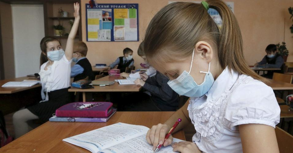 4.fev.2016 - Crianças usam máscaras durante uma aula de matemática na escola Yuri Gagarin, na cidade siberiana de Divnogorsk, na Rússia. Autoridades regionais instruíram funcionários de creches e instituições educacionais a usar máscaras para prevenir contra a propagação do vírus H1N1. A epidemia tem atingido várias regiões russas e já causou a morte de mais de cem pessoas