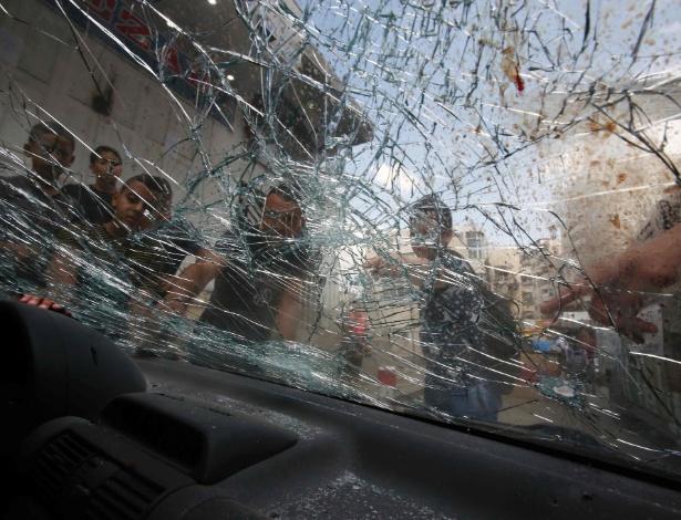 Meninos olham para carro de palestino que foi morto por forças de segurança israelenses após tentativa de ataque, em Jerusalém Oriental