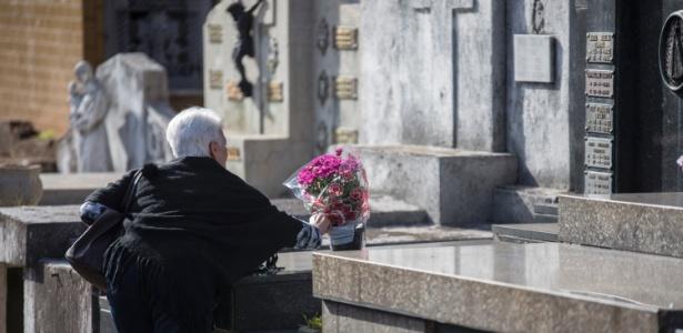 Idosa deixa flores em túmulo no dia de Finados no Cemitério do Araçá, na região central da capital paulista