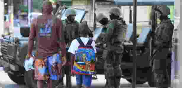 7.mar.2018 - Homem leva criança a escola em meio a operação das Forças Armadas - Jose Lucena/Futura Press/Estadão Conteúdo