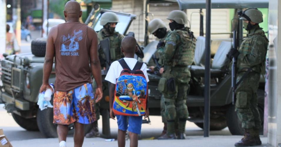 7.mar.2018 - Homem leva criança à escola em meio à operação das Forças Armadas na Vila Kennedy, zona oeste do Rio, que acontece dois dias após criminosos terem refeito as barricadas que bloqueavam as vias e que haviam sido destruídas pelo Exército