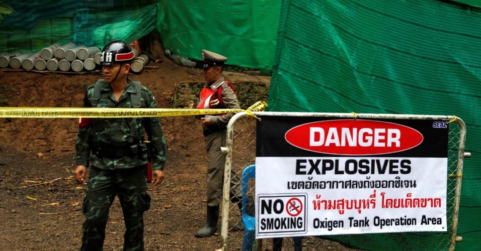 8.jul.2018 - Um policial e um soldado montam guarda em frente ao complexo de cavernas Tham Luang, onde 12 estudantes e seu treinador de futebol estão presos dentro de uma caverna inundada, depois que o governo da Tailândia instruiu membros da mídia a se retirarem urgentemente, na província de Chiang Rai