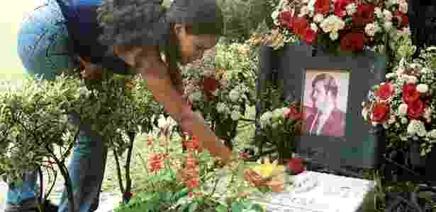 Mulher põe flores no túmulo de Pablo Escobar, em Medellin - Reuters