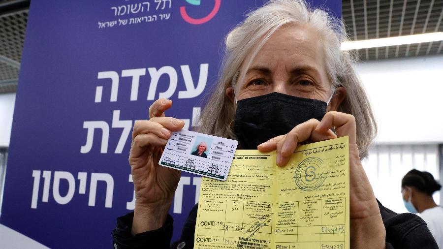 Trabalhadora israelense da área médica mostra seu certificado de vacinação contra covid após tomar a segunda dose do imunizante da Pfizer - Jack GuezG/AFP