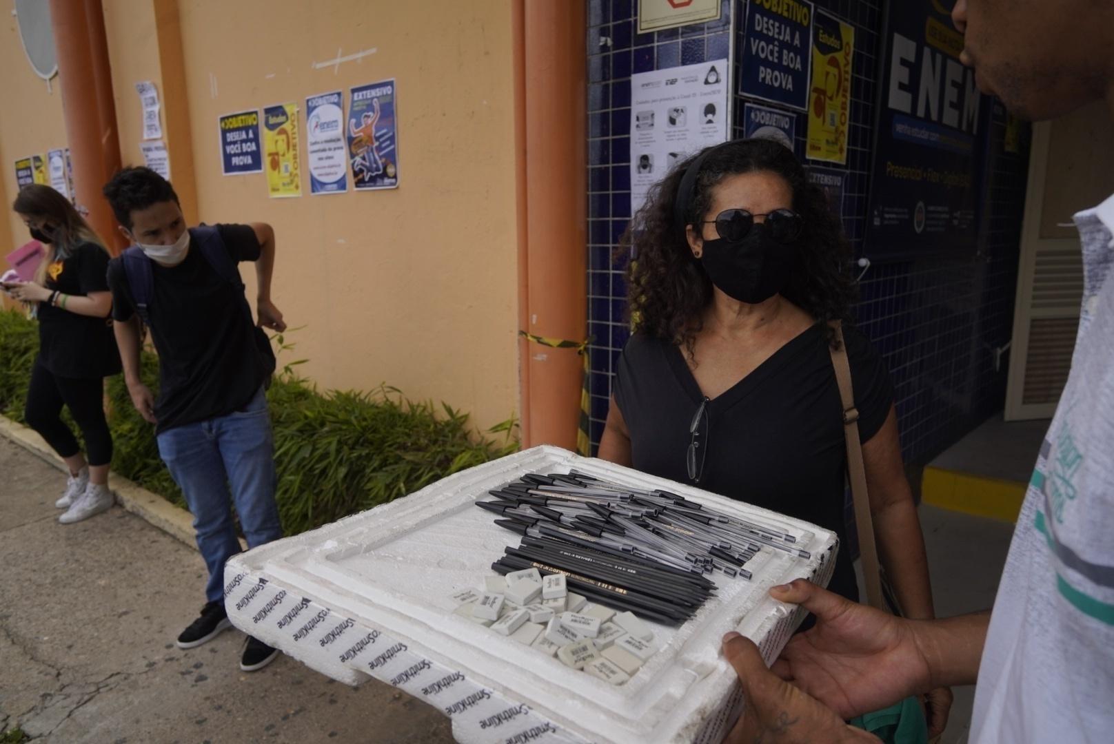 Ambulante vende caneta preta, lápis e borrachas na porta de universidade em São Paulo no 1º dia de prova do Enem impresso - André Porto/UOL
