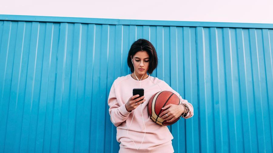 Mulher usa fones de ouvido no celular e segura bola de basquete - Getty Images/Westend61