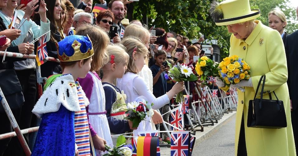 26.jun.2015 - Rainha Elizabeth II recebe flores de um grupo de crianças durante passeio pela praça Pariser Platz, próximo ao Portão de Brandenburg, em Berlim