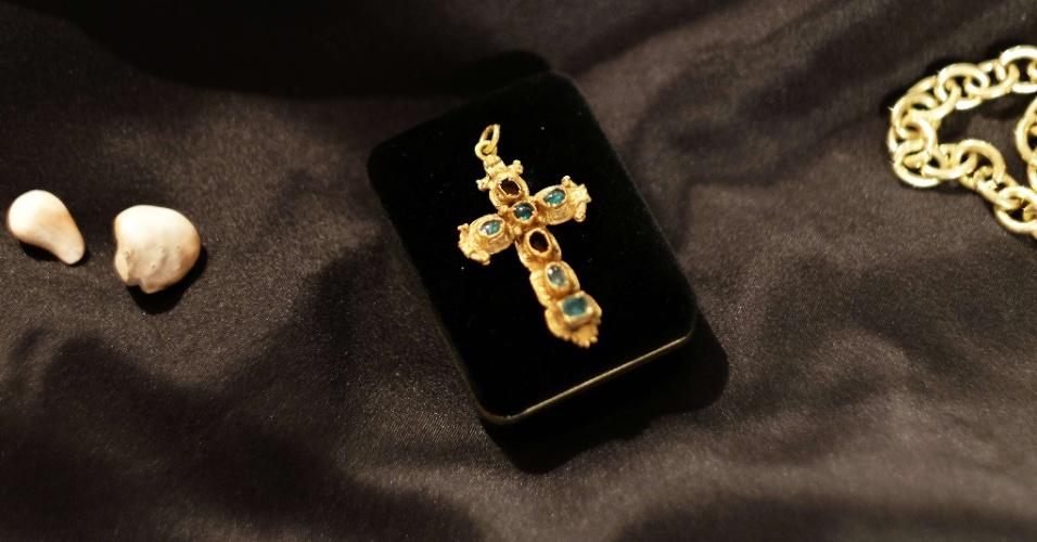 6.jul.2015 - Um crucifixo cravado de esmeraldas é exposto por um funcionário da casa de leilões Guernsey's, em Nova York (EUA), nesta segunda-feira (6). Ele faz parte do tesouro encontrado entre os destroços do navio espanhol Nuestra Señora de Atocha, que naufragou na costa da Flórida (EUA) em 1622, após ser abatido por um furacão. Um cálice, uma barra de ouro e um crucifixo cravejado com esmeraldas irão a leilão na próxima semana. As peças foram encontradas por um caçador de tesouros norte-americano na embarcação, carregada com as riquezas do Novo Mundo. Ela afundou quando fazia seu caminho de volta à Espanha