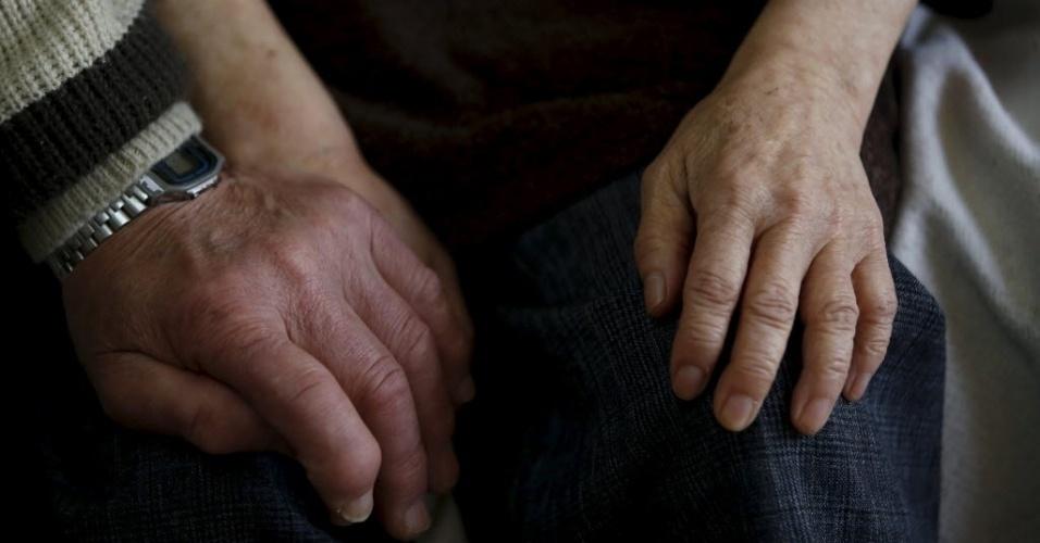 18.abr.2016 - Cerca de 11 mil pessoas com demência foram dadas como desaparecidas em 2014, a maioria temporariamente. Outros são abusadas ou mesmo mortas por parentes. Gestores públicos e especialistas acreditam que a difusão de mensagens positivas como as de Masahiko Sato podem ajudar os idosos, por acreditarem que ficar em casa ou em pequenas casas de repouso são soluções melhores que grandes instituições, pois, segundo eles, elas podem agravar a condição dos pacientes. Na imagem, Kanemasa Ito segura a mão da mulher, Kimiko, que há 11 anos foi diagnosticada com demência
