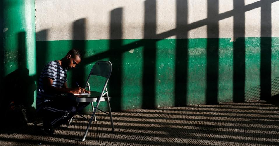 17.nov.2016 - Sob a sombra de uma cerca, imigrante somali preenche formulário em posto de imigração de Tapachula, em Chiapas, México. O objetivo do homem é chegar aos EUA