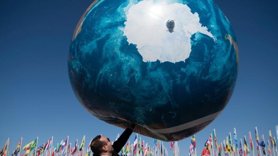 Um membro de uma delegação internacional brinca com um globo gigante fora da conferência do clima COP - Fadel Senna/AFP