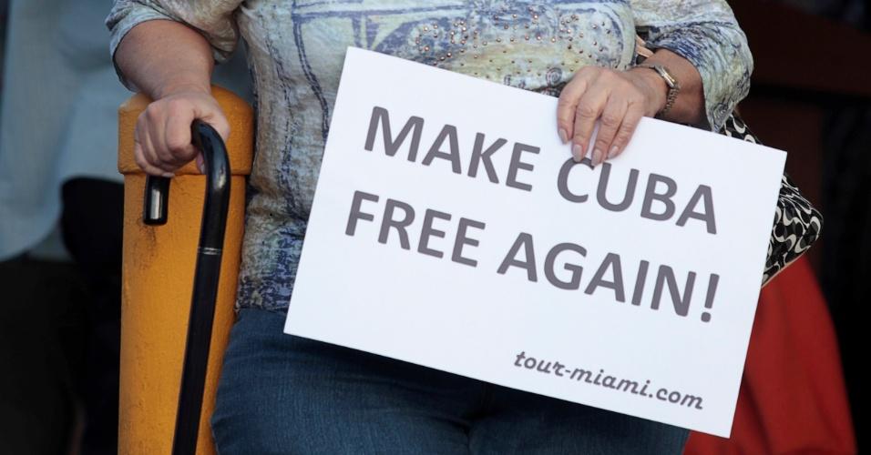 """27.nov.2016 - A cubana Caridad Hernandez segura a placa """"Tornar Cuba livre novamente"""" em frente ao popular cubano Café Versailles em Miami"""