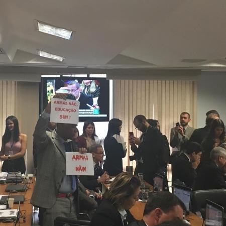 O deputado Pastor Sargento Isidório (Avante-BA) levanta cartazes contra o decreto das armas na CCJ do Senado - Hanrrikson de Andrade/UOL
