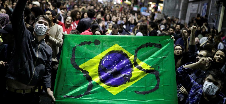Manifestantes fazem protesto escrevendo S.O.S na bandeira do Brasil em São Paulo - Nacho Doce/Reuters