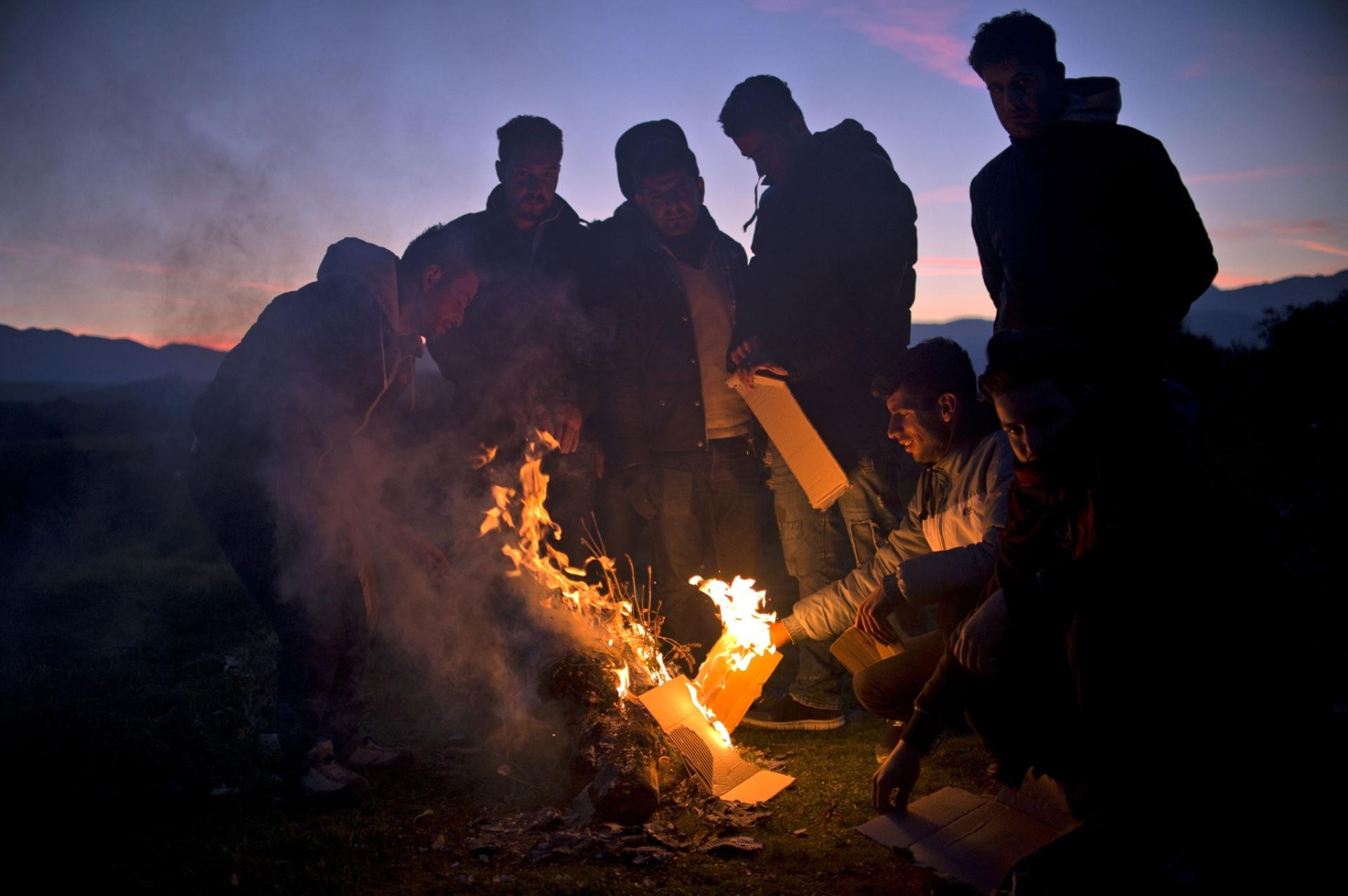 4.nov.2015 - Refugiados fazem fogueira para se aquecer enquanto esperam para entrar em acampamento, depois de terem atravessado a fronteira entre Grécia e Macedônia. Mais de 218 mil refugiados atravessaram do mediterrâneo para a Europa em outubro mais do que toda a onda migratória em 2014, segundo a ONU (Organização das Nações Unidas)