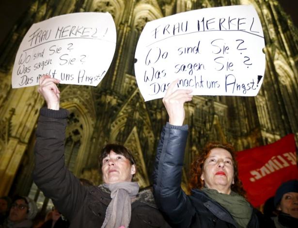 """Mulheres seguram cartaz onde se lê """"Sra. Merkel, onde está você? O que diz? Isso nos amedronta!"""", durante protesto em frente à catedral de Colônia, na Alemanha"""