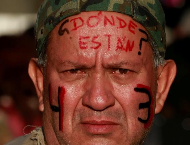 """Manifestante com o número 43 e a pergunta """"onde estão?"""" pintandos no rosto participa de marcha pelo 28º mês de desaparecimento de 43 estudantes no Estado de Guerrero, na Cidade do México"""