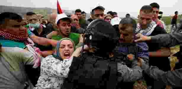 Palestinos tentam impedir que manifestante seja preso por soldados israelenses durante protesto na Cisjordânia - Mohamad Torokman/Reuters