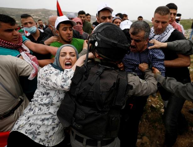 Palestinos tentam impedir que manifestante seja preso por soldados israelenses durante protesto na Cisjordânia