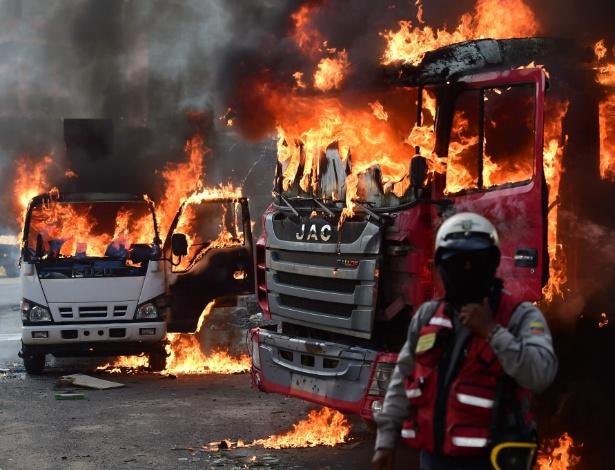 Oficial venezuelano diante de caminhões em chamas durante protesto em Caracas