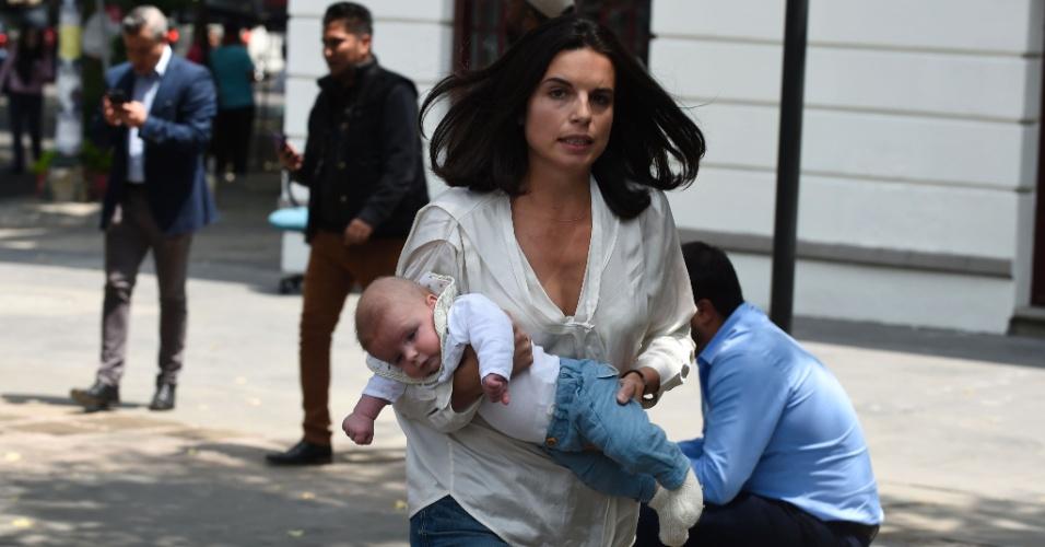 19.set.2017 - Mulher corre com bebê em rua da Cidade do México após forte terremoto atingir o local