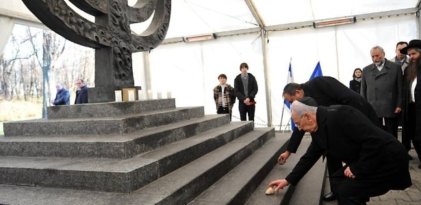 25.nov.2010 - Shimon Peres (na frente), ex-presidente de Israel, e Avigdor Lieberman, ministro da Defesa de Israel, colocam pedras em monumento do holocausto em Babi Yar, na Ucrânia
