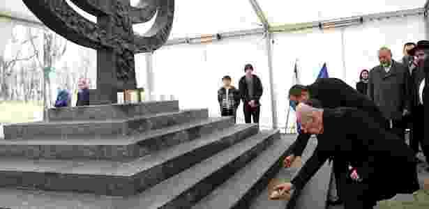 25.nov.2010 - Shimon Peres (na frente), ex-presidente de Israel, e Avigdor Lieberman, ministro da Defesa de Israel, colocam pedras em monumento do holocausto em Babi Yar, na Ucrânia - Genya Savilov/AFP