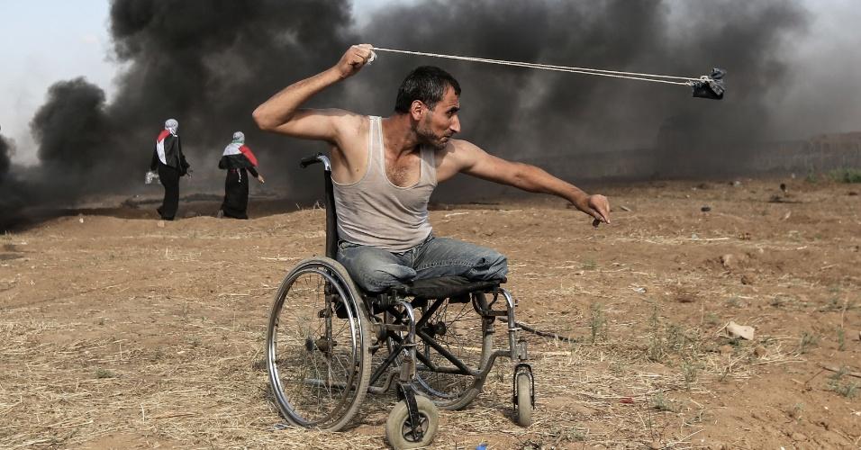 O palestino Saber al-Ashkar, 29, lança pedras na direção das forças israelenses em Gaza