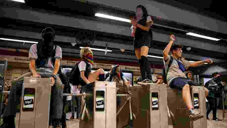 Manifestantes pulam catraca no metrô de Santiago, no Chile - JAVIER TORRES / AFP