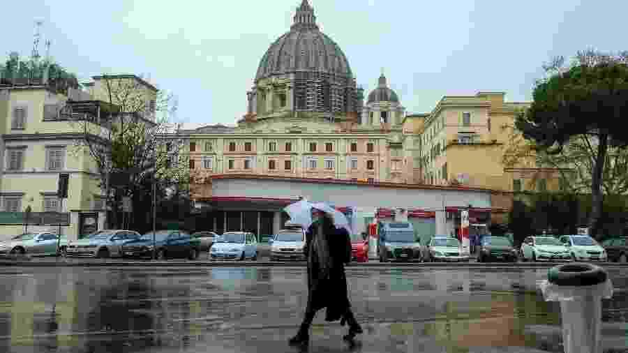 26.mar.2020 - Coronavírus: de máscara, mulher caminha próximo à Basílica de São Pedro, no Vaticano, Itália - Andreas Solaro/AFP