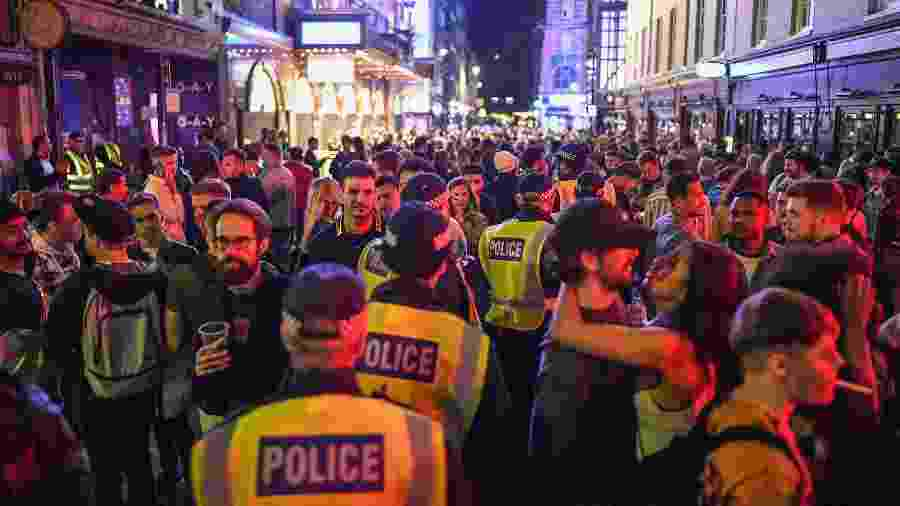 Policiais andam em meio à aglomeração da reabertura dos bares no Soho, em Londres, após a pandemia de coronavírus - Getty Images