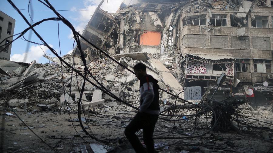 Palestino anda entre escombros de um prédio destruído durante ataques aéreos de Israel à Faixa de Gaza - Suhaib Salem/Reuters