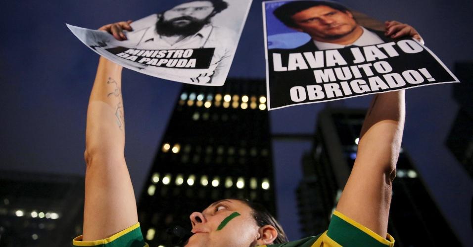 17.mar.2016 - Manifestante ergue dois cartazes, um exaltando o juiz federal Sérgio Moro e outro satirizando posse do ex-presidente Luiz Inácio Lula da Silva como ministro-chefe da Casa Civil, durante ato que pede a renúncia da presidente Dilma Rousseff