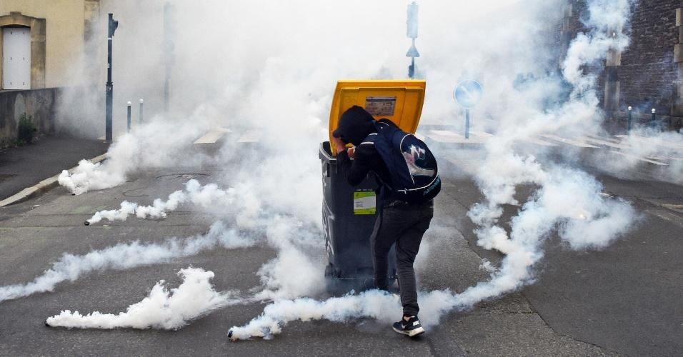 17.mai.2016 - Manifestante se protege de bombas de gás lacrimogêneo jogadas pela polícia local durante um protesto em Rennes (349 km de Paris), na França. Ele participava de uma manifestação contra reformas na legislação trabalhista planejadas pelo governo francês