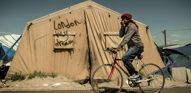 """Homem passa diante de barraca com os dizeres """"Londres meu sonho"""", no campo de refugiados em Calais, França"""
