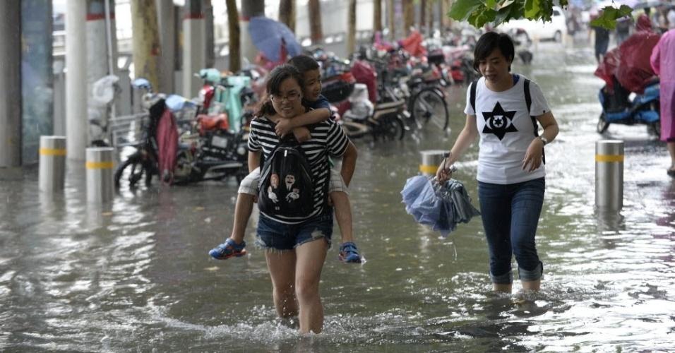 5.ago.2016 - Moradores caminham por área alagada em Zhengzhou, em Henan, na China