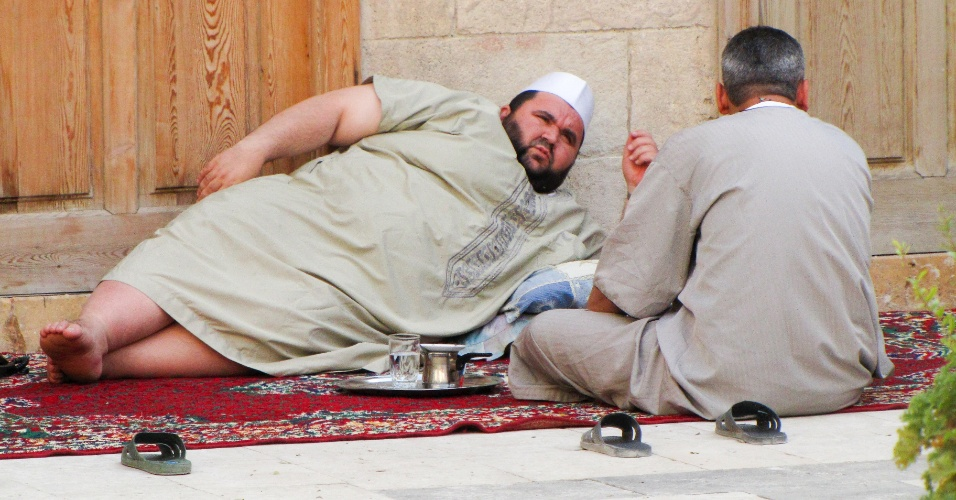 Homens descansam e tomam chá no pátio da mesquita Umayyad entre as preces islâmicas. A cena era comum em mesquitas de Aleppo pré-guerra