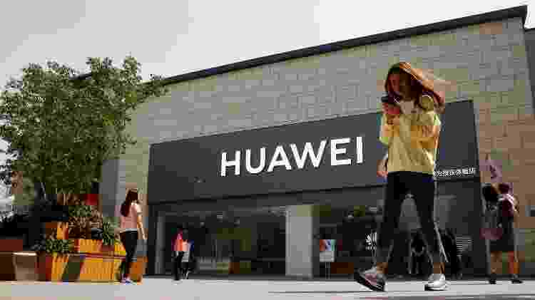 Mulher olha para o telefone enquanto passa por uma loja da Huawei em Pequim, China - Thomas Peter/Reuters