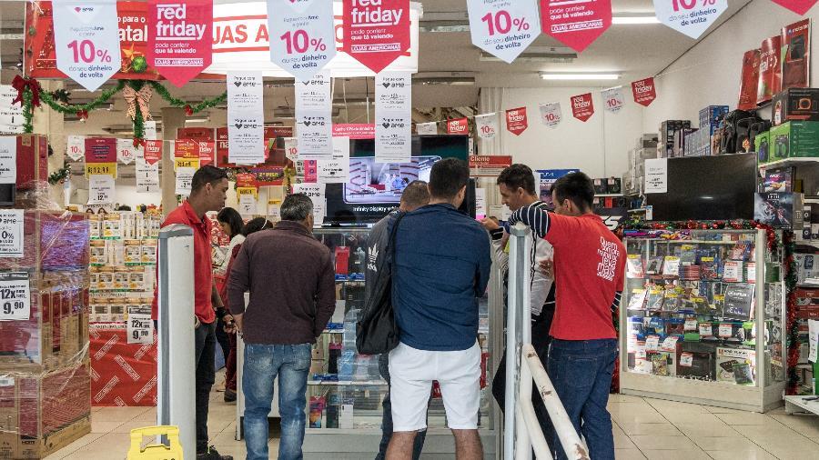 29.nov.2019 - Consumidores passam em loja, no centro de São Paulo, para ver promoções de Black Friday - Simon Plestenjak/UOL
