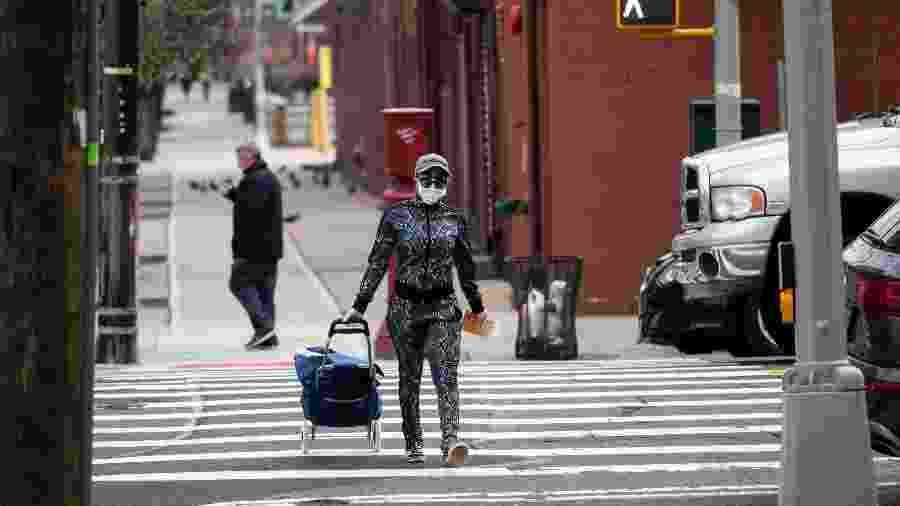 Mulher com máscara carrega carrinho de compras em Nova York, nos Estados Unidos - Johannes EISELE / AFP