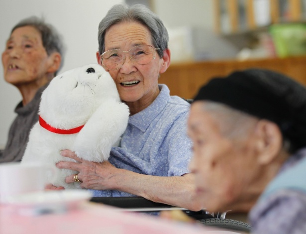 """Mulher no Japão segura o robô Paro, feito para """"cuidar"""" de idosos - Kim Kyung-Hoon/ Reuters"""