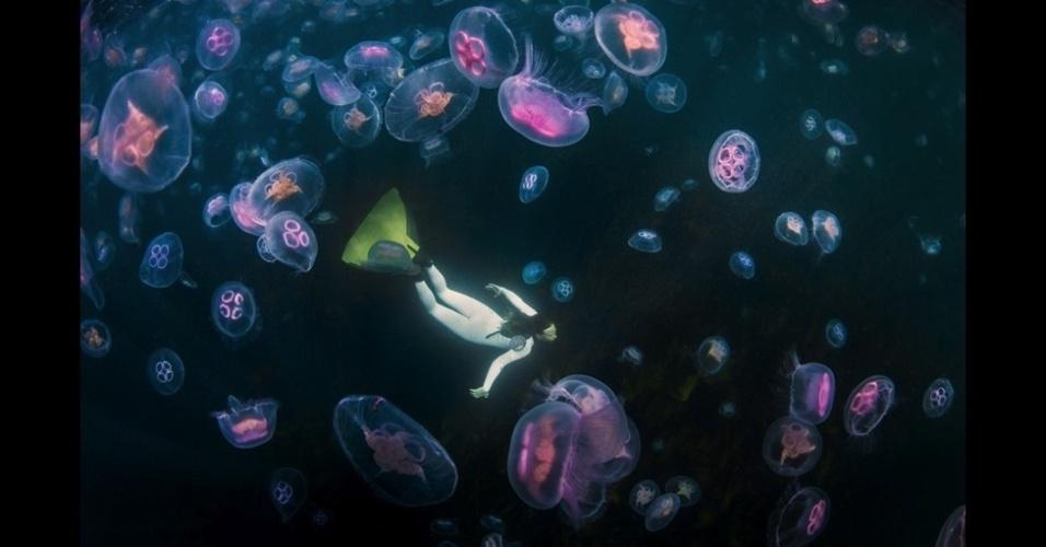 """4.jan.2016 - Mergulhador nada com medusas-da-lua na foto de George Karbus. A imagem ficou em primeiro lugar na categoria """"Under Exposed"""" (baixa exposição)"""