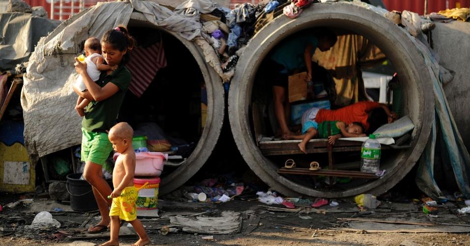 22.mar.2016 - Famílias improvisam e fazem de tubos de concreto abandonados suas moradias em rua de Manila. De acordo com dados do governo das Filipinas, cerca de um quarto da população, que tem aproximadamente 100 milhões de habitantes, vive na pobreza, sobrevivendo com um dólar por dia