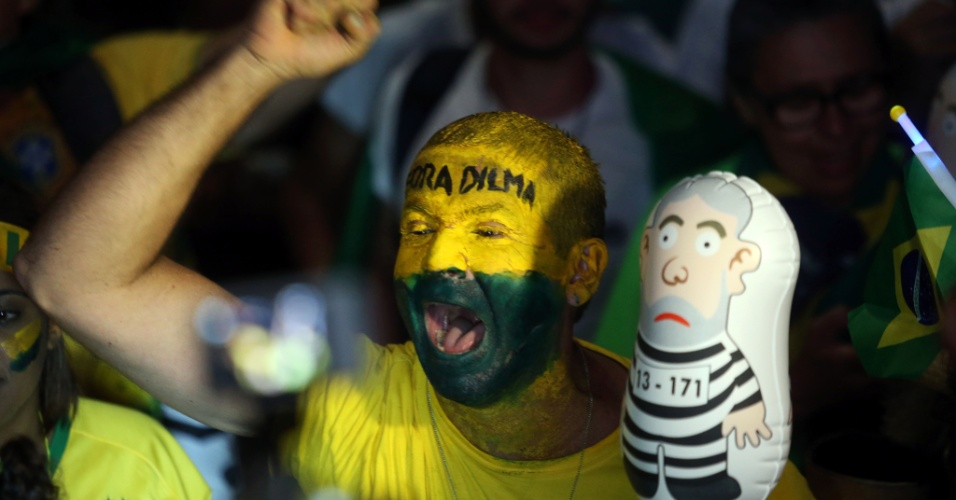 """17.abr.2016 - Com o rosto pintado de verde e amarelo e a frase """"Fora Dilma"""", manifestante comemora na praia de Copacabana, no Rio, a aprovação do processo de impeachment da presidente na Câmara"""