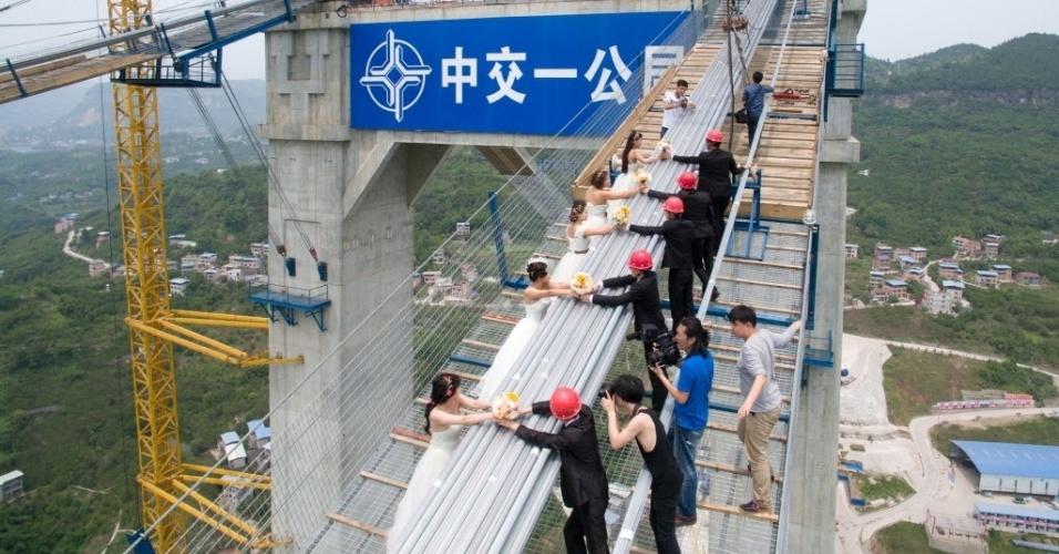 4.mai.2016 - Casais fazem fotos de casamento em uma ponte suspensa sobre o rio Yangtze, na China. Oito casais participaram de uma festa temática no Dia Nacional da Juventude da China