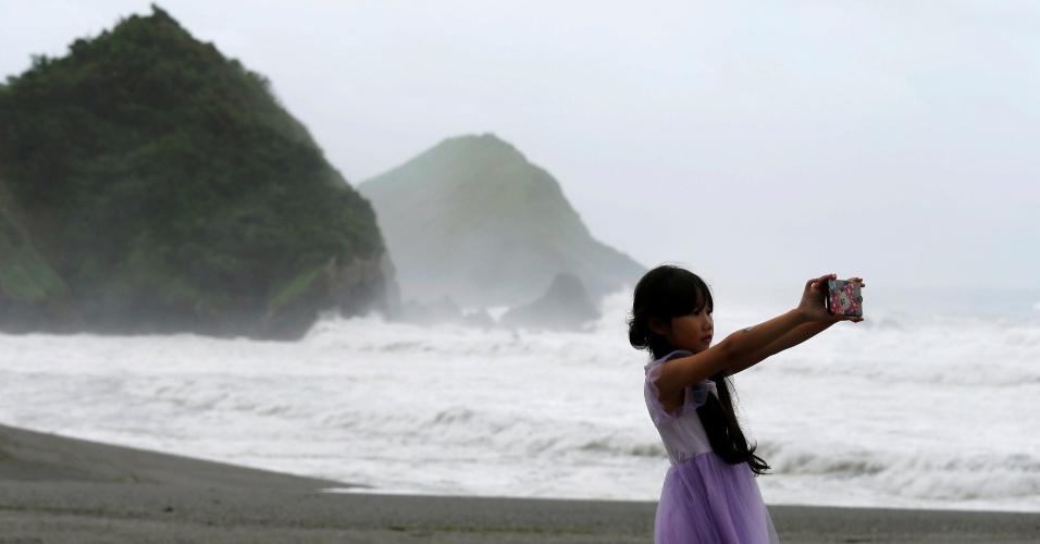 7.jul.2016 - Menina faz selfie tendo as fortes ondas em Yilan, em Taiwan, como plano de fundo, enquanto o tufão Nepartak se aproxima da ilha chinesa