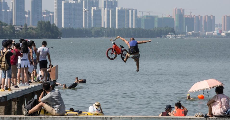 24.jul.2016 - Homem pula em lago com bicicleta durante evento local para convocar residentes a proteger o meio ambiente em Wuhan, na China